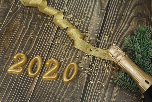 Garrafa de champanhe com enfeites de natal dourados, fita e confetes e 2020 em números