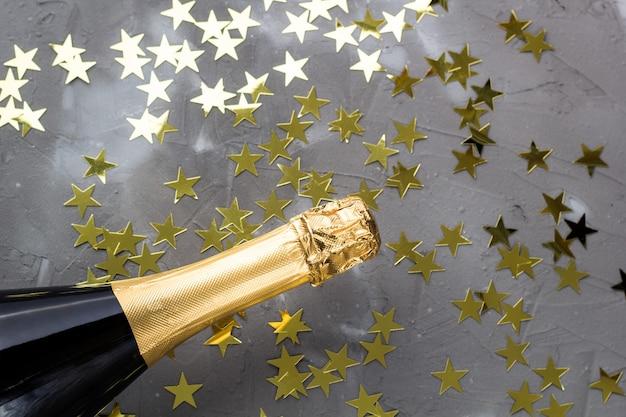 Garrafa de champanhe com estrelas douradas de confete. conceito de natal, ano novo, aniversário ou casamento