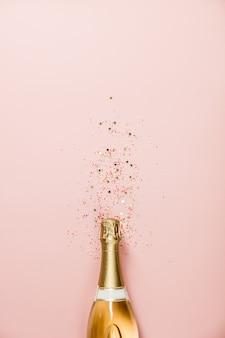 Garrafa de champanhe com granulado em fundo rosa