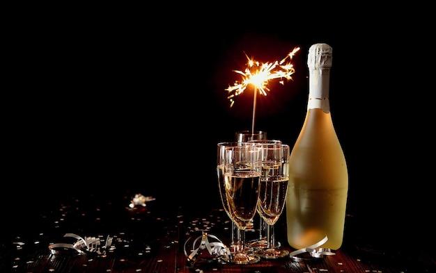 Garrafa de champanhe com taças de champanhe na mesa escura, fogo bengali