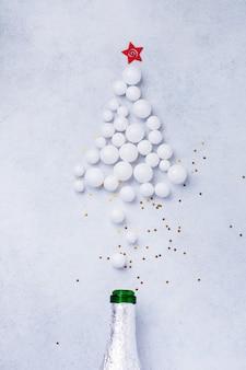 Garrafa de champanhe de natal com granulado cor branco sobre branco.
