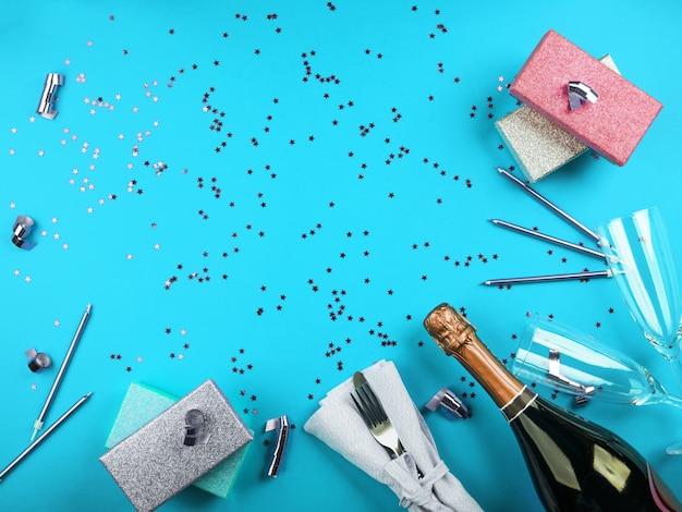 Garrafa de champanhe e confetes com presentes em fundo azul