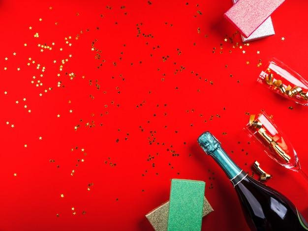 Garrafa de champanhe e confetes com presentes em fundo vermelho