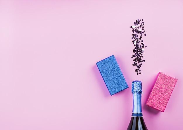 Garrafa de champanhe e confetes com presentes no fundo rosa