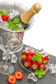 Garrafa de champanhe e duas taças fundo branco arranjo de morangos espumante