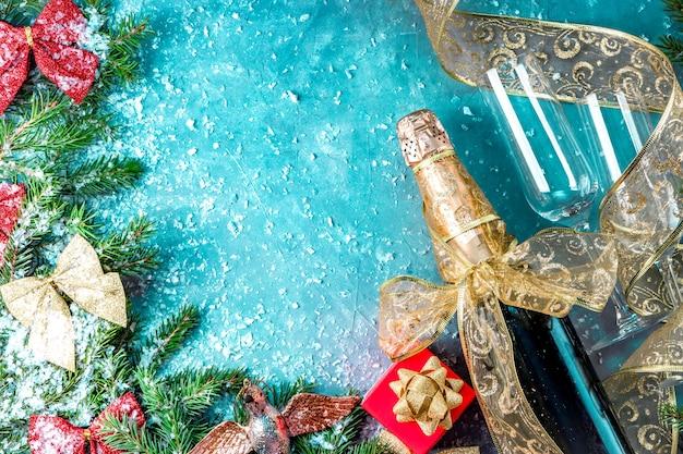 Garrafa de champanhe e duas taças na neve e decorações de natal