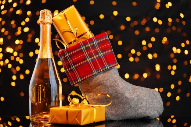 Garrafa de champanhe e meia de natal com presentes contra guirlanda