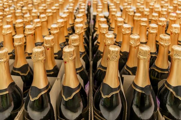 Garrafa de champanhe e muitas filas de garrafas com tampas douradas.