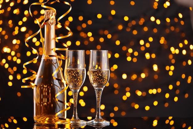 Garrafa de champanhe e taças em fundo de luzes desfocadas
