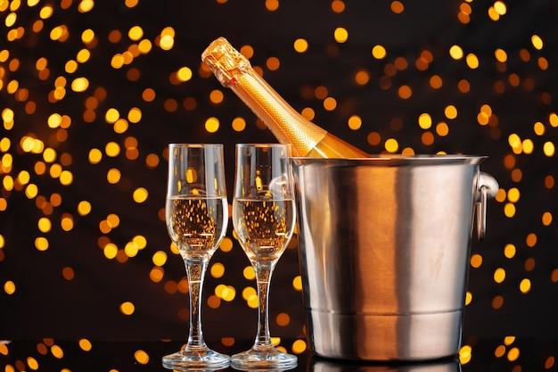 Garrafa de champanhe e taças na vista frontal do fundo de luzes desfocadas