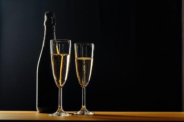 Garrafa de champanhe e taças sobre fundo escuro