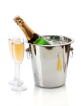 Garrafa de champanhe em balde com gelo e taças de champanhe, isolada no branco