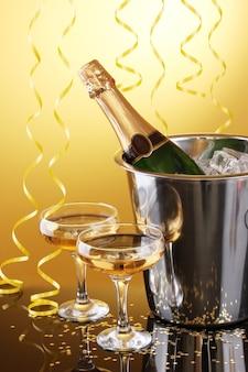 Garrafa de champanhe em um balde com gelo e taças de champanhe, em fundo amarelo