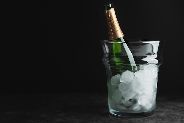 Garrafa de champanhe em um balde de gelo com espaço de cópia