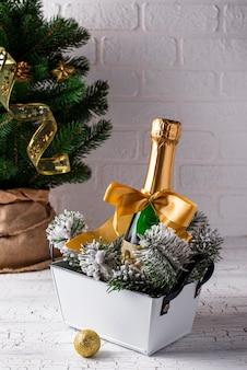 Garrafa de champanhe em uma embalagem de ouro com decoração de natal