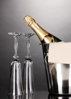 Garrafa de champanhe no balde com gelo e copos