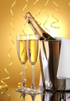 Garrafa de champanhe no balde com gelo e taças de champanhe
