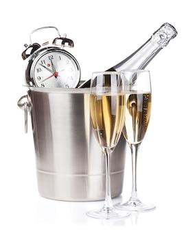 Garrafa de champanhe no balde, duas taças e despertador. isolado em fundo branco