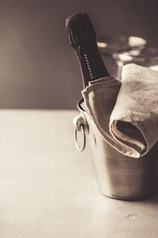 Garrafa de champanhe no balde e copos em fundo de concreto
