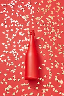 Garrafa de champanhe pintado de vermelho de natal simulada em um fundo de férias coberto de abetos vermelhos brilhantes pequenos com espaço de cópia. cartão de férias.