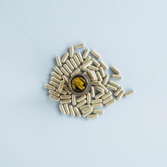 Garrafa de comprimidos rodeada de cápsulas sobre fundo colorido