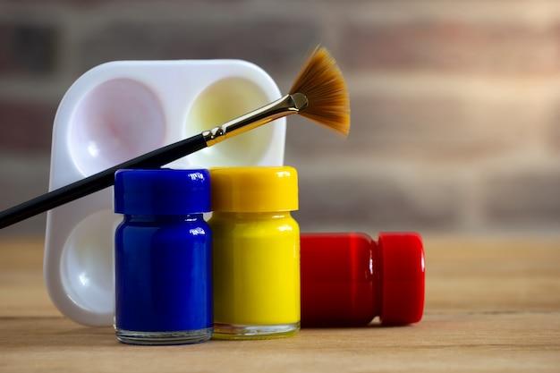 Garrafa de cor de cartaz, pincel e paleta na mesa de madeira