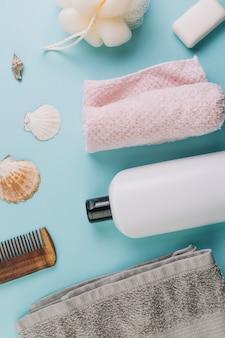 Garrafa de cosméticos perto de toalhas e ancinho