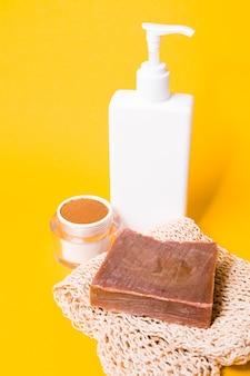 Garrafa de creme sem rótulo lenço de café e sabonete caseiro em fundo amarelo cuidados com o corpo em casa