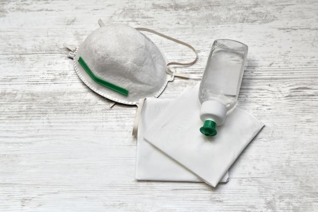 Garrafa de desinfetante para as mãos em lenços ao lado de uma máscara de poeira em uma mesa de madeira branca