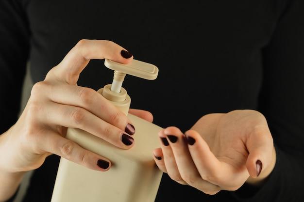 Garrafa de desinfetante para as mãos ou sabão nas mãos femininas, close-up vista. imagem discreta de produtos genéricos de higiene pessoal, limpeza e autocuidado