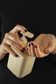 Garrafa de desinfetante para as mãos ou sabão nas mãos femininas