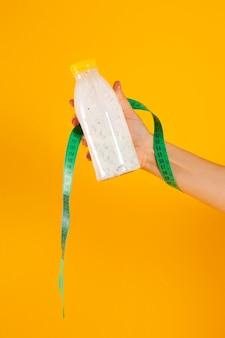 Garrafa de iogurte com sementes de chia em uma mão no estúdio em um fundo amarelo