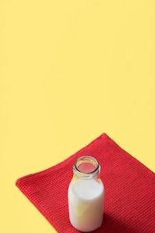 Garrafa de leite aberta no guardanapo vermelho sobre o fundo amarelo