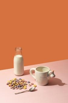 Garrafa de leite, cereais coloridos e um copo com um unicórnio em uma superfície rosa