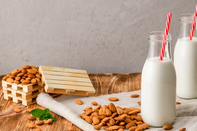 Garrafa de leite de amêndoas em uma mesa de madeira branca com amêndoas e hortelã
