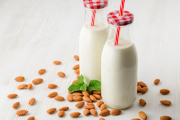 Garrafa de leite de amêndoas em uma mesa de madeira branca, com amêndoas e verde.
