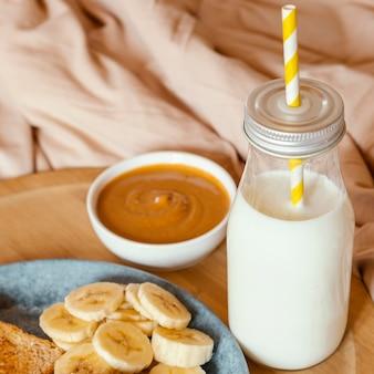 Garrafa de leite de ângulo alto, bananas e manteiga de amendoim