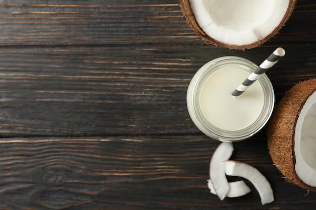Garrafa de leite de coco com palha, coco e fatia de coco na mesa de madeira. vista do topo