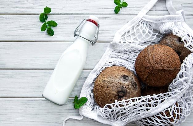 Garrafa de leite de coco e cocos em uma bolsa de malha ecológica em uma mesa de madeira
