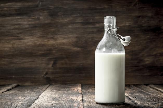 Garrafa de leite de vaca fresco. sobre um fundo de madeira.