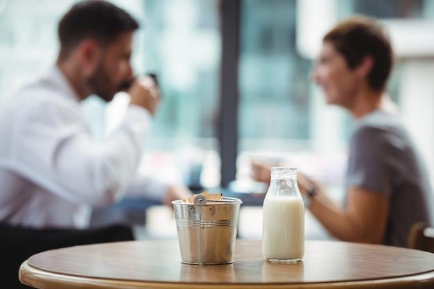 Garrafa de leite e balde na mesa