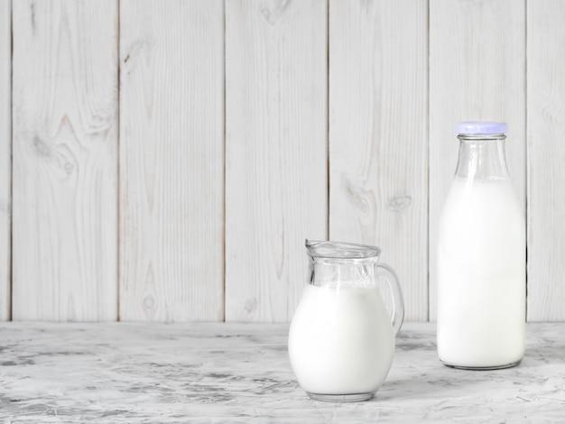 Garrafa de leite e uma jarra de leite em uma mesa cinza