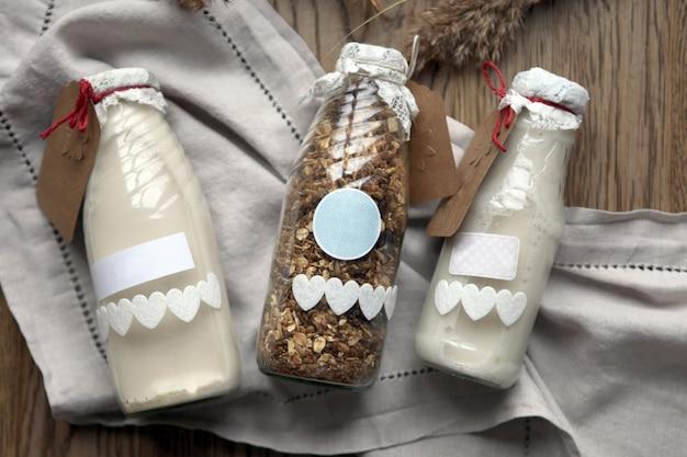 Garrafa de leite fresco com aveia e grãos de trigo integral em flocos na mesa de madeira. muesli ou leite de granola caseiro ou iogurte em fundo de madeira rústico