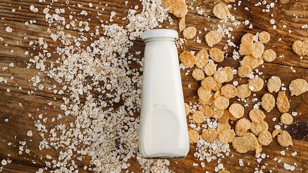 Garrafa de leite fresco na superfície de madeira com aveia e cereais. conceito de comida saudável e natural