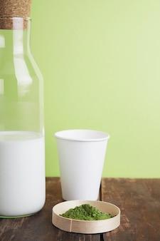 Garrafa de leite vintage, papel branco leva vidro e pó de chá matcha premium orgânico na mesa de madeira escovada marrom na frente de um fundo verde simples. fechar-se