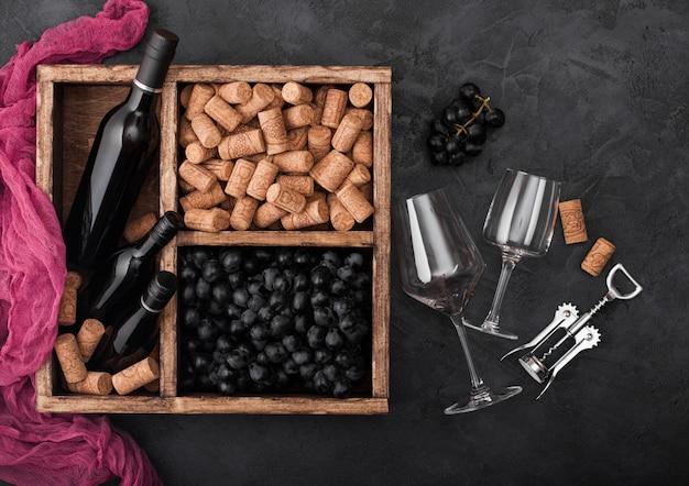 Garrafa de luxo de vinho tinto e copos vazios com uvas escuras com rolhas e saca-rolhas dentro da caixa de madeira vintage.