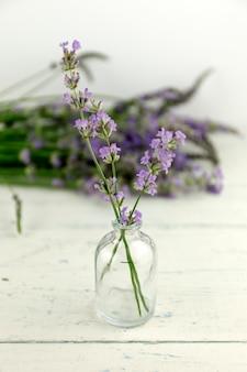 Garrafa de óleo de ervas e flor de lavanda na madeira shaby