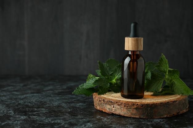 Garrafa de óleo de essência de urtiga na mesa preta esfumada