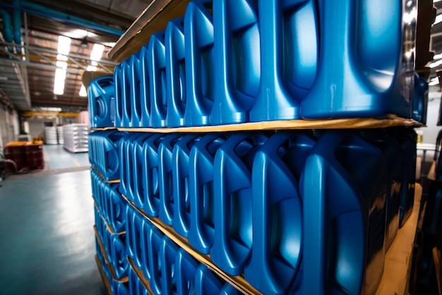 Garrafa de óleo de motor de plástico em paletes são armazenadas na fábrica do armazém para serem embaladas