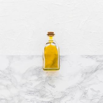 Garrafa de óleo de vidro fechado no pano de fundo texturizado